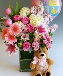 Lilies, roses, and hydrangea are among elegant greens and other florals in all pink. Premium Design includes 9