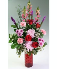 This vivid arrangement brings red roses together with bright gerbera daisies and mums.  The lush arrangement comes in a tall red vase, and is accented by a glimmering heart.