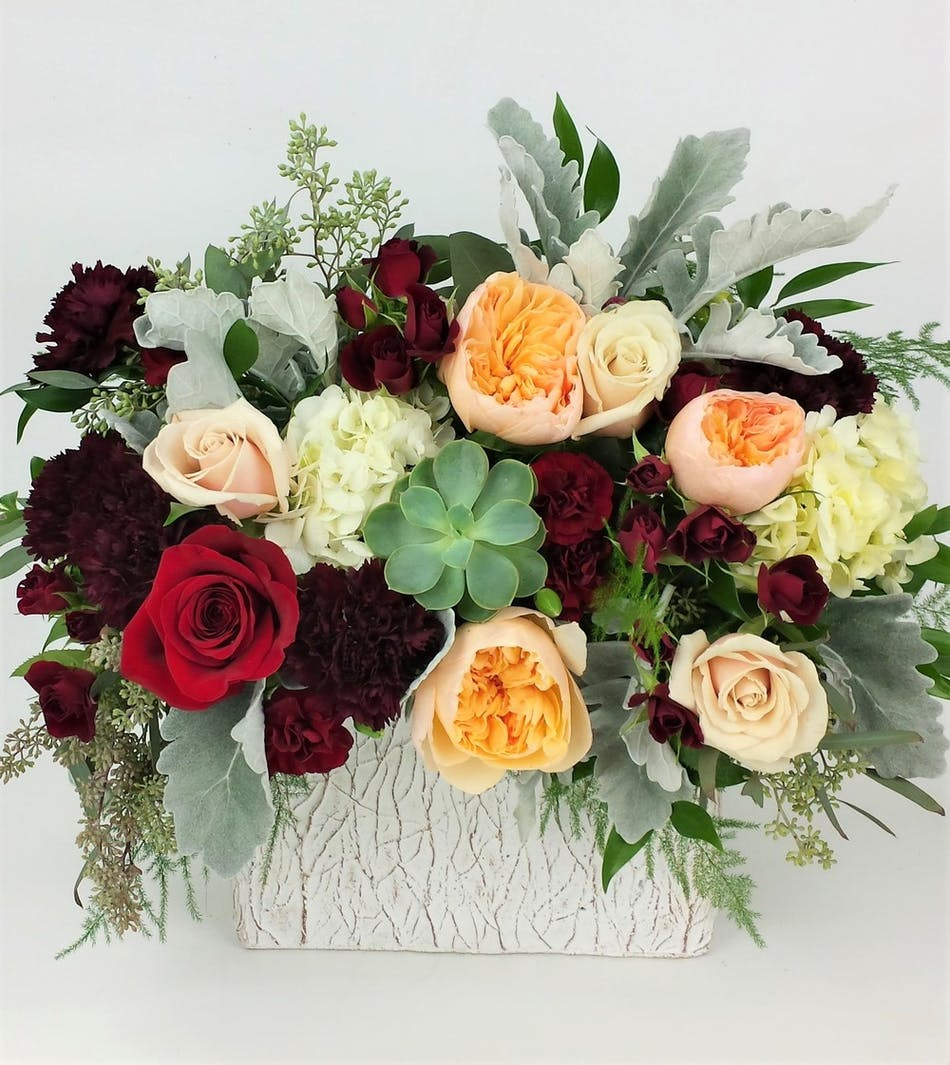 Fresh and Modern design with our freshest seasonal flowers, such as roses, succulents and hydrangea. Designed in a handcrafted heavy red glass vase for a quality keepsake.