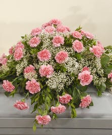 A classic casket design featuring pink carnations and white babies breath with lush greenery.