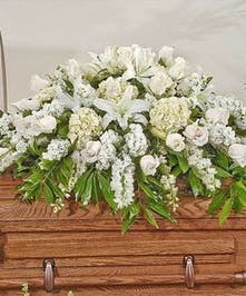 Elegant white casket spray featuring Roses, Lilies, and orchids along with other white accent