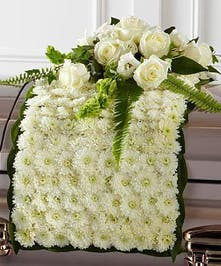 White chrysanthemums form a blanket of blooms that drape across the casket accented with an arrangement of white roses, bells of Ireland, and a variety of lush greens.