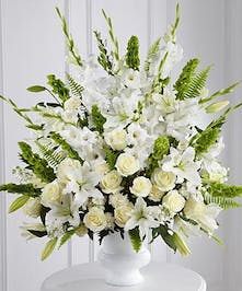 Lily, bells of Ireland, roses and mixed flowers combine to create an elegant display of flowers.