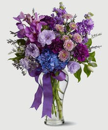 fragrant blossoms in cool shades of lavender, purple and blue, accented with a matching purple ribbon. orchids, carnations, and fresh flowers.