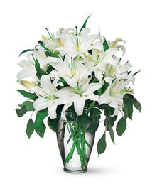 Fragrant white Oriental lilies are accented with seeded eucalyptus in an elegant clear vase.