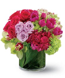 A mix of premium flowers in contrasting pink and green colors in our signature, leaf-wrapped vase.