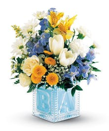 Add your warmest congratulations with a delightful bouquet filling a crystal block with happy blossoms. It's stork-ready, with same-day delivery.