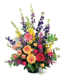 This outstanding arrangement of vibrant seasonal flowers offers your condolences in a most memorable way.