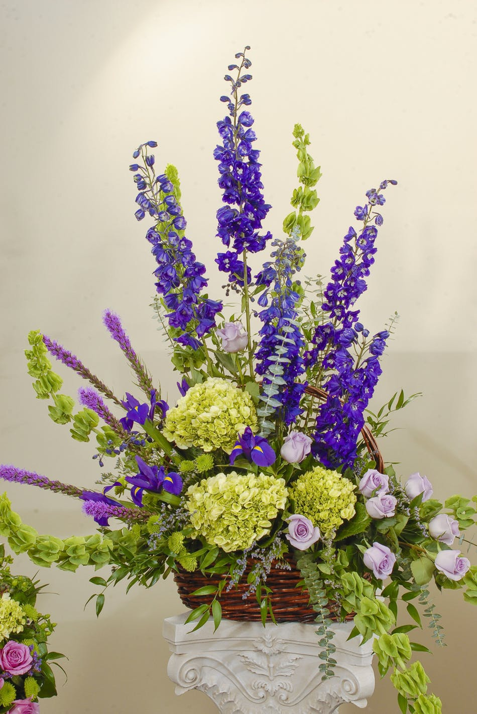 Basket design featuring roses and hydrangea in a mix of purple, green, and blue hues. Approximate size for the standard design is 20