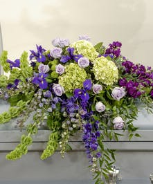 A casket designed in a stunning color combination of purples, blues and lime green, that features roses, hydrangea, delphinium, and other coordinating flowers.