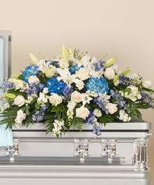 Blue and white casket spray features a mix of roses, delphinium, hydrangea and other accenting flowers.