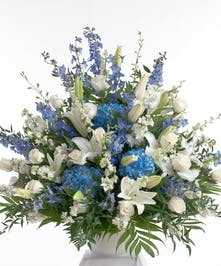 Stunning blue and white fan shaped arrangement designed in a white urn.  Featuring a mix of flowers including hydrangea, lilies, and roses.