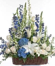 Floor basket design featuring an assortment of blue and white flowers including roses, delphinium, and hydrangea. Approximate size for the standard design is 20