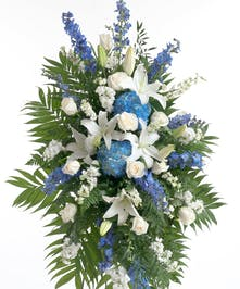 Mix of roses, delphinium, hydrangea and other accenting flowers in blue and white. Displayed on an easel creating a big impression in any sized room.