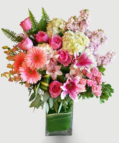 This beautiful design in shades of pink features our leaf wrapped signature clear vase. Lilies, roses, and hydrangea are among other floral textures and elegant greenery