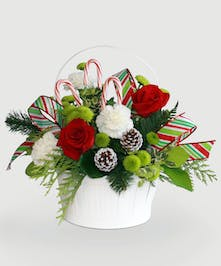 Festive white basket filled with traditional holiday colors and candy cane accents.
