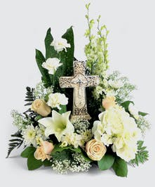 A revered Symbol of Love. This arrangement features a ceramic cross surrounded by all white flowers. Roses, hydrangea and carnations combine for a beautiful tribute.