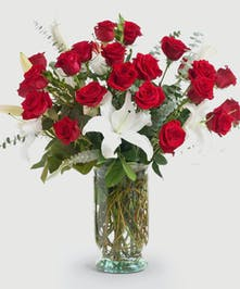 Classic mix of premium long stem red roses and white lilies in a clear glass vase. Approximate size of standard design is 16