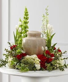 Roses, hydrangea, and other accenting red and white flowers create an ideal setting for the celebration of life. Approximate size of standard design is 18
