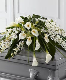 A modern casket display in all white featuring classic calla lilies and dendrobium orchids with tropical foliage.
