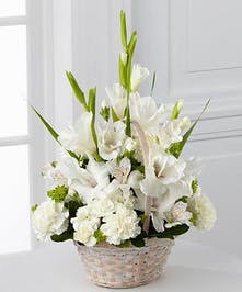 White gladiolas, white alstroemeria, and mini carnations nestled with fresh greens in a handled basket .
