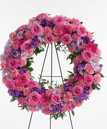Wreath display featuring a mix of lush pink and lavender flowers including roses, carnations, and daisy's displayed on an easel.