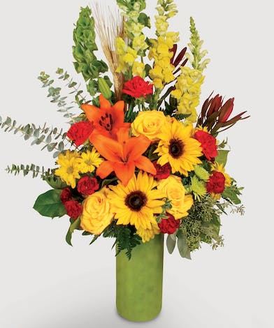 Orange , Yellow, and red created with roses, sunflowers, and carnations and other fresh flowers will brighten any room.