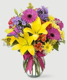 Brightly colored spring flowers, including lilies, gerbera daisies, and carnations, in a crystal clear glass vase. Tied with a coordinating bow and cute butterfly pick!