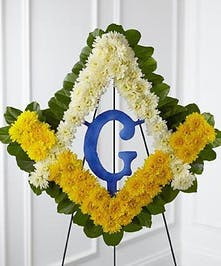 A display of the Freemason symbol created with white and yellow chrysanthemums and lush greens.