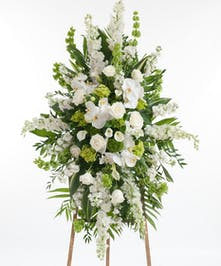 Premium collection of our finest white and green blooms featuring white roses, orchids, calla lilies, hydrangea, and other premium accents displayed on an easle.