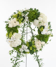White orchids, Calla lilies, hydrangea, roses, and other premium accents. Wreath display features  the finest white flowers available.
