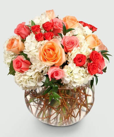 arrangement of white hydrangea, coral, orange, and peach roses will keep them smiling and thinking of you! Created in a large clear glass keepsake bowl.