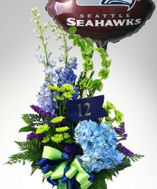 This bright green and blue arrangement in a tall, Hawks-green vase comes with a
