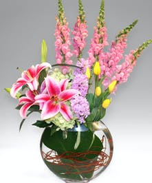 Lilies, tulips, hyacinth and more textural blooms displayed in sleek, glass moon-shaped vase will show your gratitude in the grandest of ways.