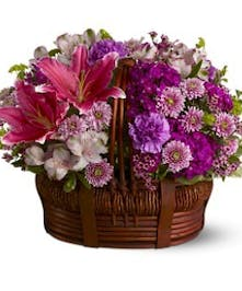 Lavender roses, pink Asiatic lilies, lavender daisies, purple matsumoto asters, green hypericum berries and lush greens are sweetly arranged in a square whitewash basket