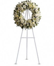 Wreath display filled with classic white flowers including roses, lilies, and chrysanthemum. Approximate size of the standard design is 18
