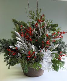 Freshly cut evergreens and berries displayed in a black outdoor pot.