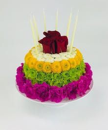 Send this Bright Birthday Cake! It includes fresh, brightly colored flowers, such as mini carnations and daisy mums all topped off with a rose.