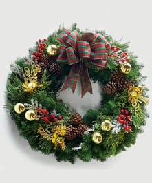 This locally-made, custom wreath of lush evergreens has a traditional plaid bow, snowy accents and red berries with gold accents throughout