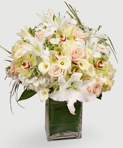 Beautiful white flowers combine with blush colored roses, exotic green orchids, fragrant stock, and captivating white lilies in our signature, leaf-wrapped vase.