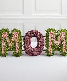 The word Mom made of roses, carnations, and chrysanthemums.