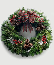 This locally-made, custom wreath of lush evergreens has a traditional plaid bow, snowy accents and red berries; a warm and fragrant way to wish happy holidays.