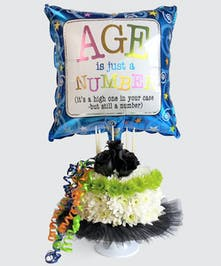 This birthday treat features a floral Cake topped with 3 black roses and a festive Balloon.