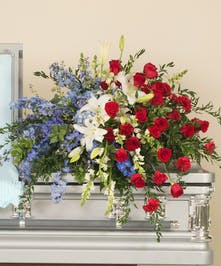 Patriotic casket spray design featuring red roses, white lilies and blue delphinium.