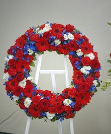 Standing wreath display featuring roses, carnations, and other floral accents with a patriotic red, white, and blue color scheme. Approximate size 18