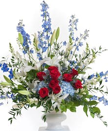 Patriotic floral design in red white and blue flowers featuring lilies, roses, and delphinium designed in a large white container. Approximate size f is 24