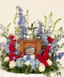 Memorial display featuring a patriotic mix of our favorite red white and blue flowers. This arrangement is designed for an urn placement. Family to provide urn .