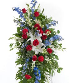 Featuring red roses, blue hydrangea, blue delphinium, and other accenting flowers.  Approximate size of  the standard design is 28