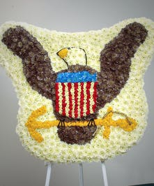 Custom patriotic eagle made of chrysanthemums displayed on an easel stand.