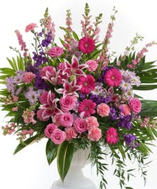 Feminine mix of lavender and pink flowers including roses, lilies, and gerbera daisy's. Flowers are designed in a large white urn container.